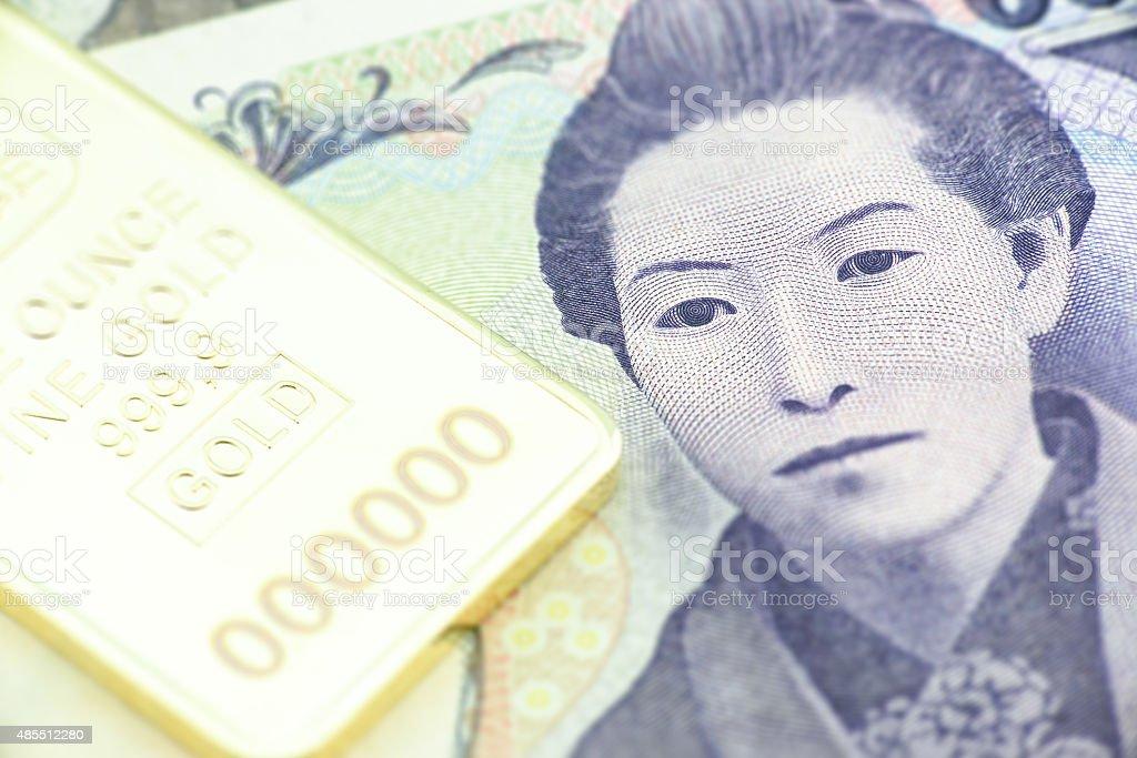 Japanese five thousand yen, a macro close-up with gold bullion. stock photo
