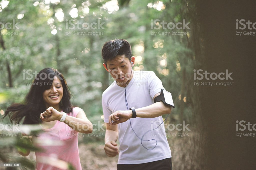 Japanese friends checking data on smartwatch while doing sport outdoors stock photo