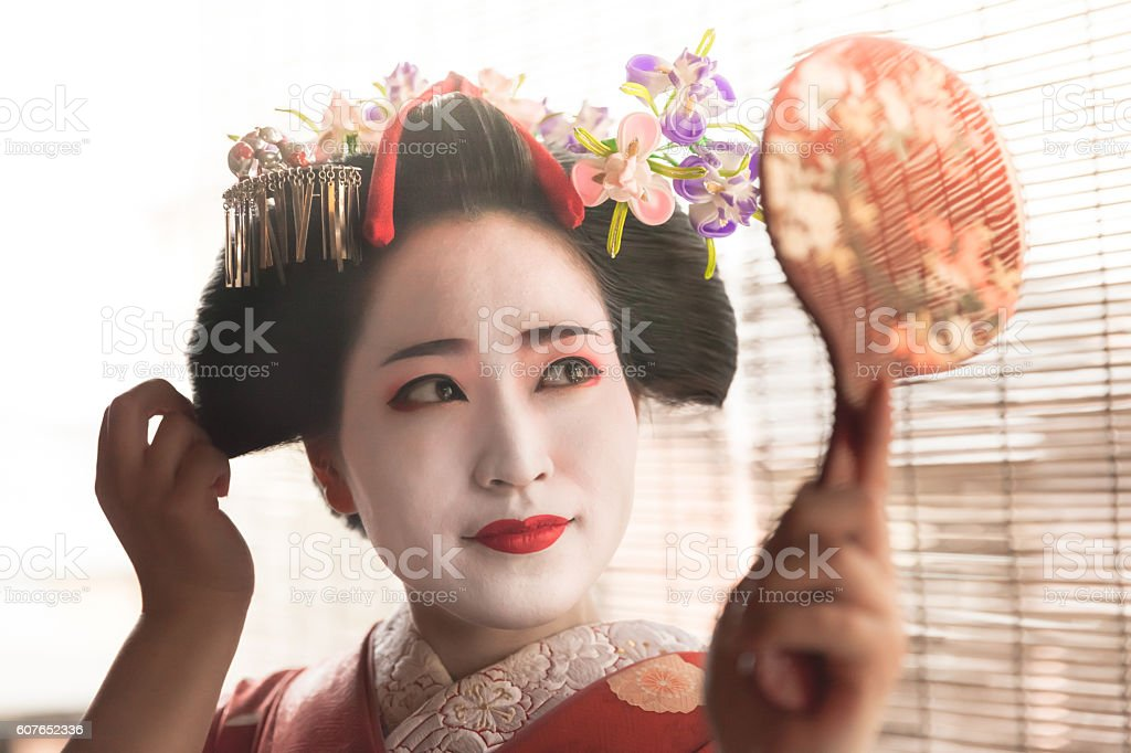 Japanese geisha looking in the mirror stock photo