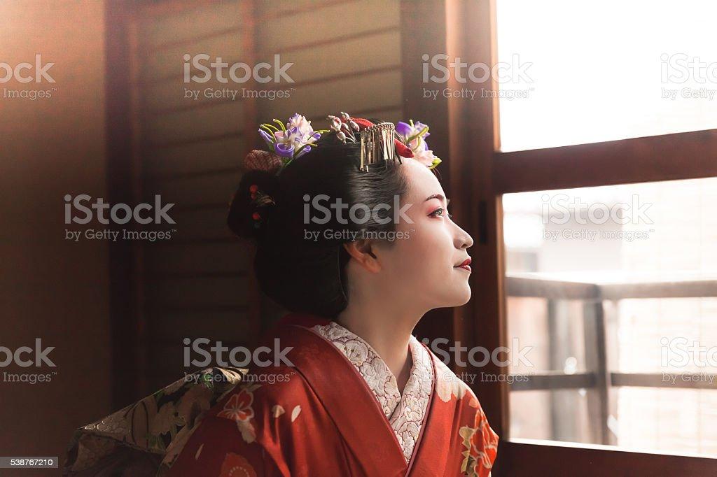 Japanese Geisha looking through the window stock photo