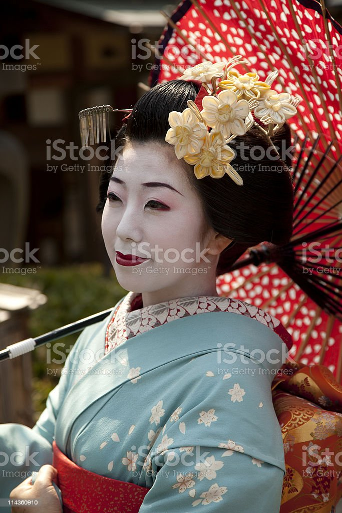 A Japanese geisha sitting all dressed up stock photo