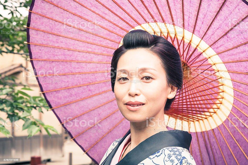 Japanese geisha  with paper umbrella in historic Kyoto stock photo