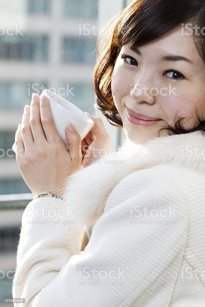 Japanese Girl Drinking Coffee in Front of Large Window royalty-free stock photo