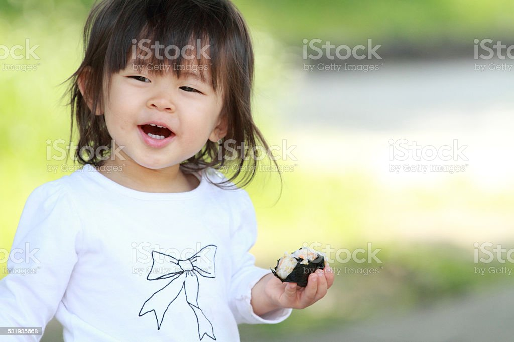 Japanese girl eating rice ball (1 year old) stock photo