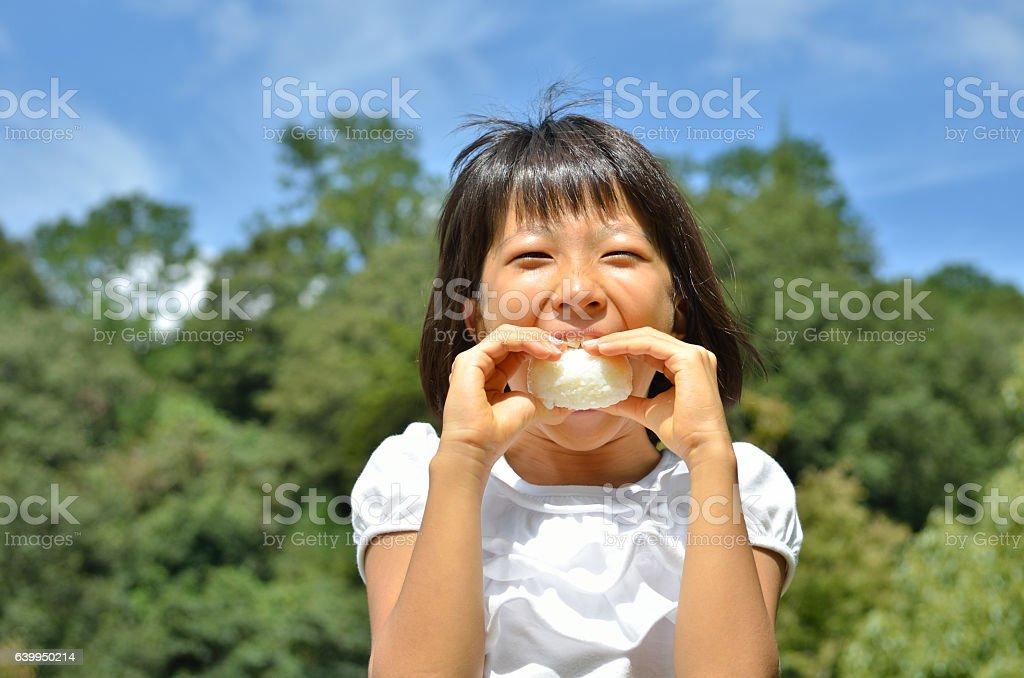 Japanese girl eating rice ball stock photo