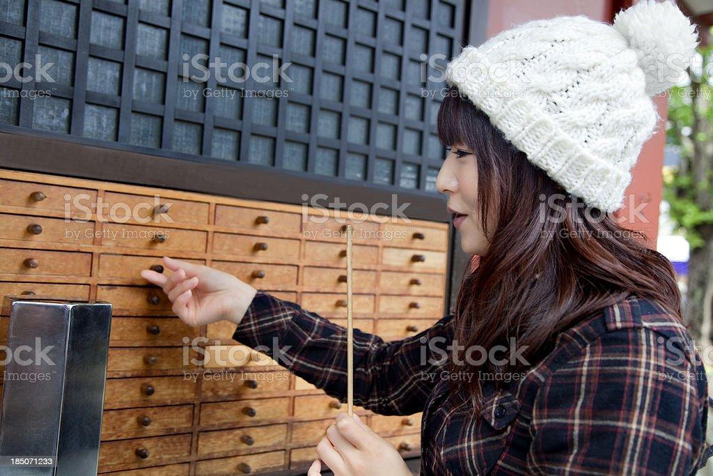 Japanese girl openin drawer with omikuji at Sensoji Temple royalty-free stock photo