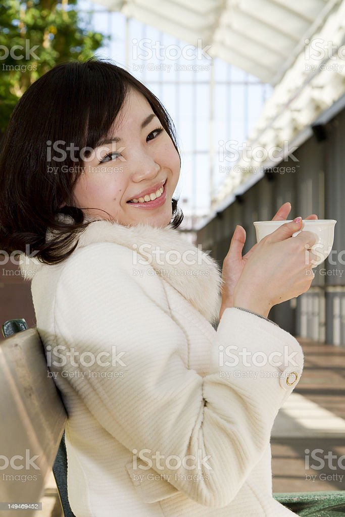 Japanese Girl Sitting on Bench and Drinking Coffee royalty-free stock photo
