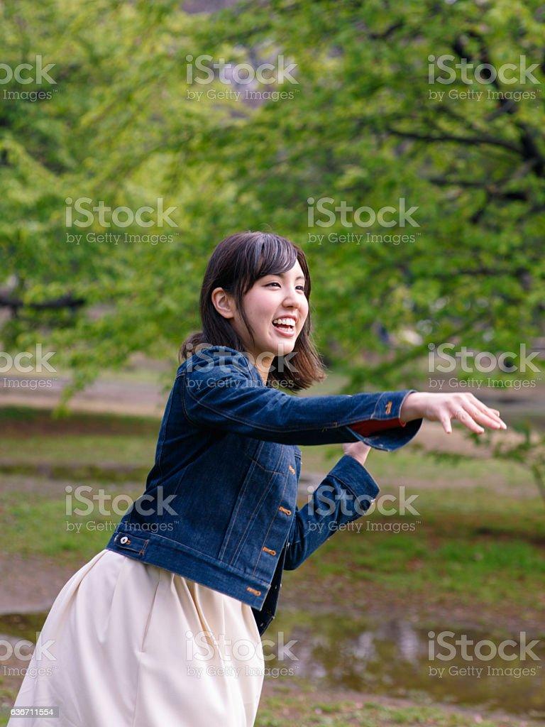 Japanese girl throwing ball at park stock photo