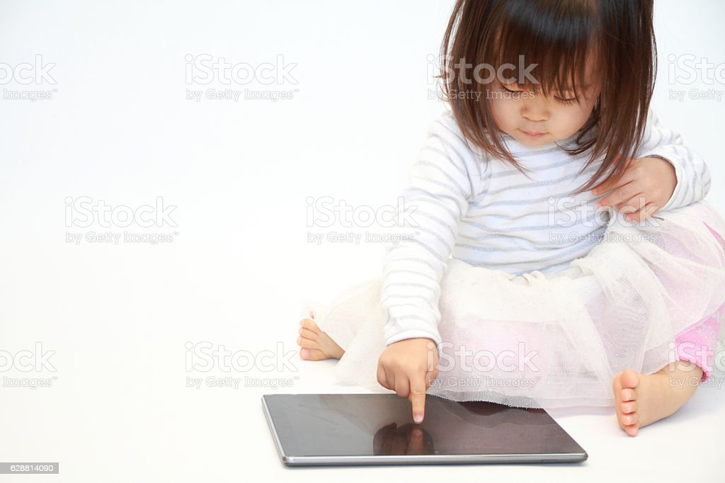 Japanese girl using a tablet PC (2 years old) stock photo