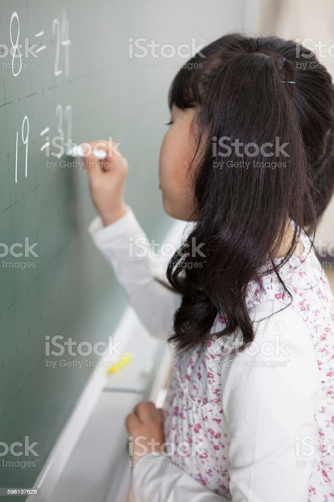 Japanese girl writing on blackboard stock photo