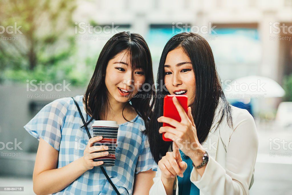 Japanese girlfriends looking at a smart phone stock photo
