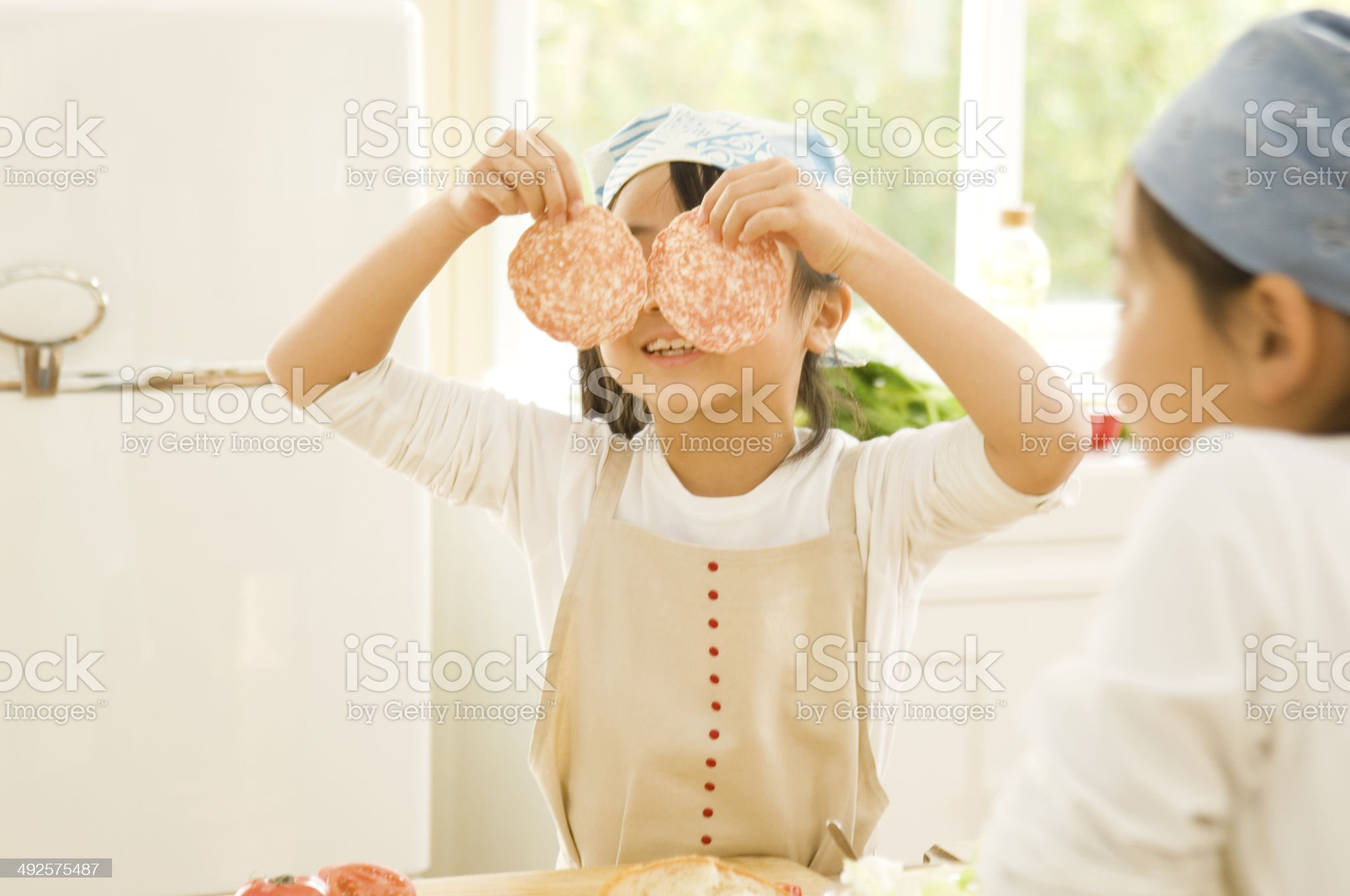 Japanese girls cooking playing with ham in kitchen royalty-free stock photo