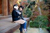 Japanese girls sitting at autumn temple