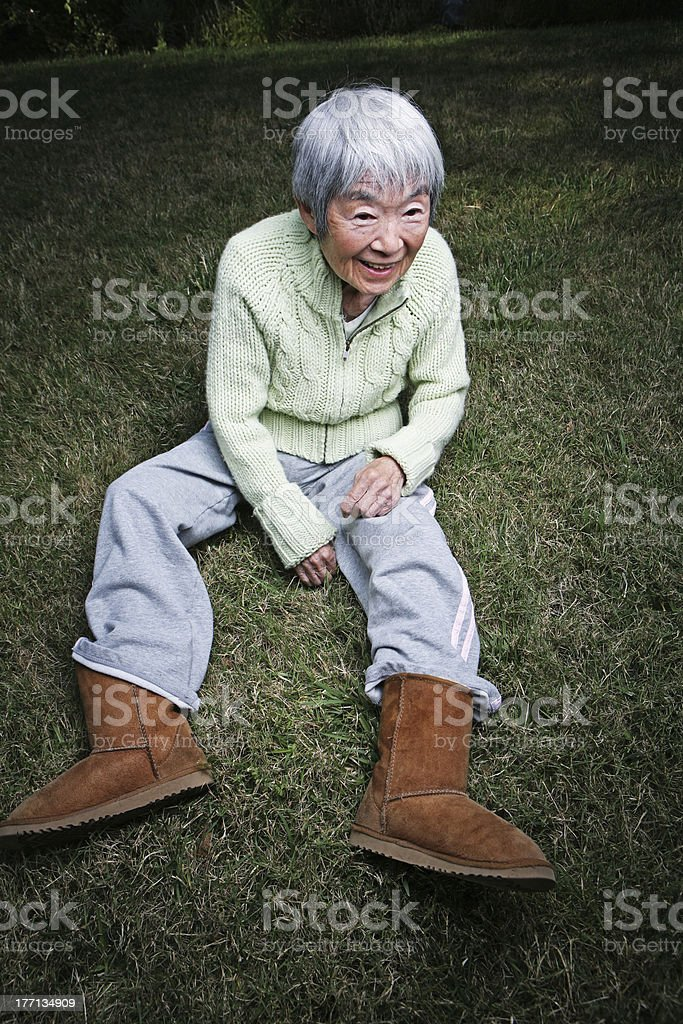 Japanese Grandma in Boots Sitting Outside stock photo