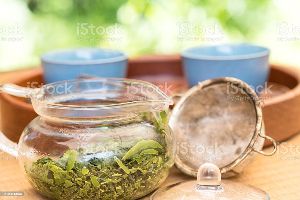 Japanese Green Tea Leaves in Teapot with Strainer and Cups stock photo
