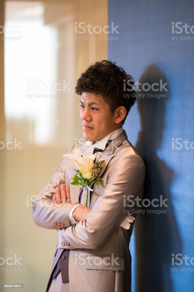 Japanese groom leaning on wall with confidence stock photo