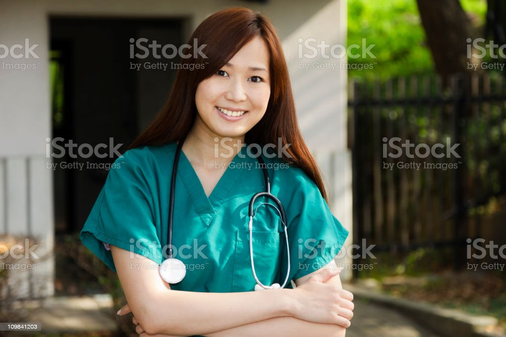 A smiling young Japanese woman wearing scrubs standing next to a...