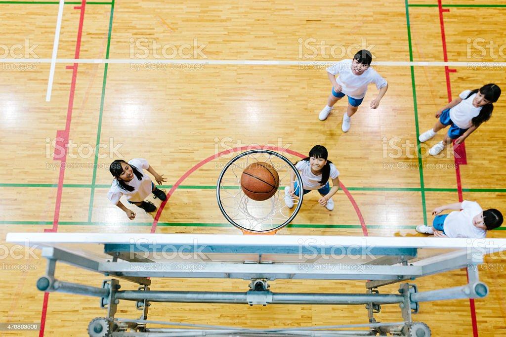 Japanese high school. A school gymnasium. Female students play basketball stock photo