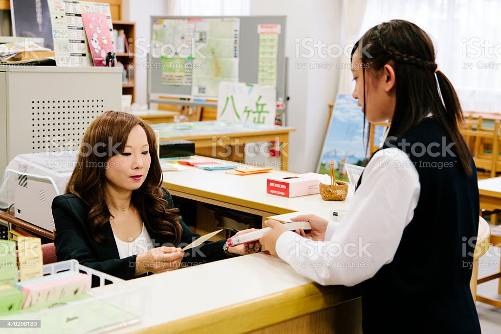 Japanese high school, borrowing a book, female student and librarian stock photo