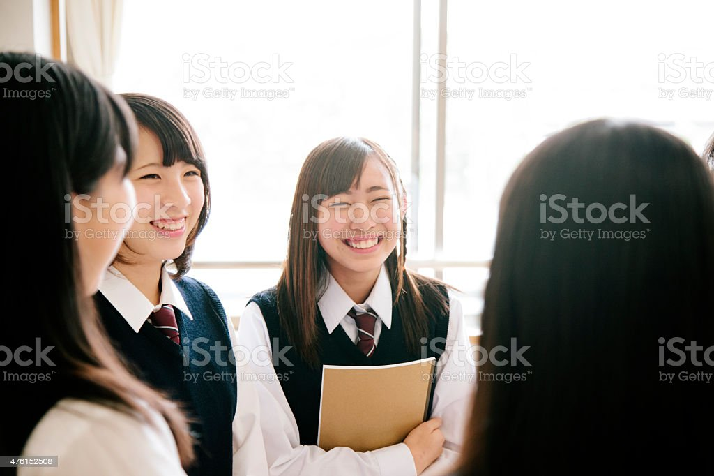 Japanese high school children, four teenaged girls chat in classroom stock photo