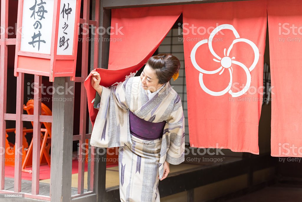 Japanese lady in Yukata looking outside from shop stock photo