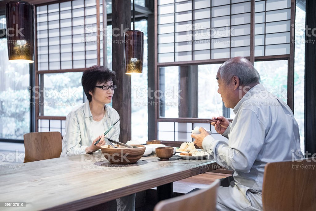 Japanese man and woman sitting at table eating dinner stock photo