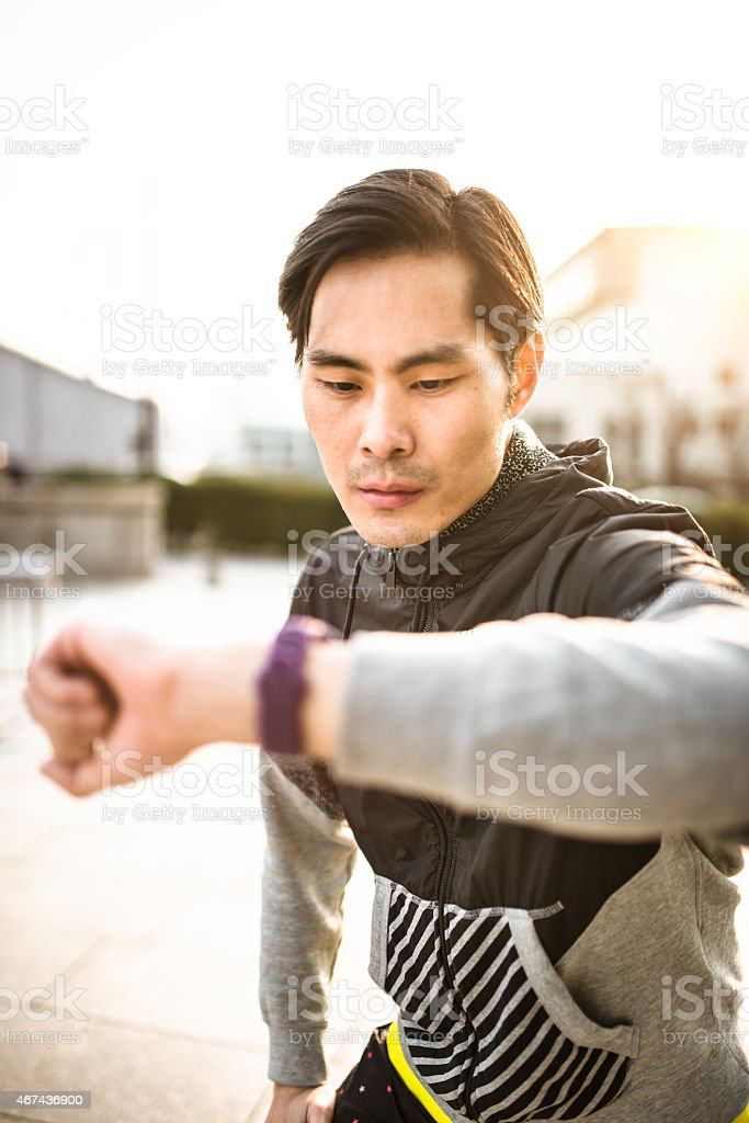 Japanese man checking the time and doing sport stock photo
