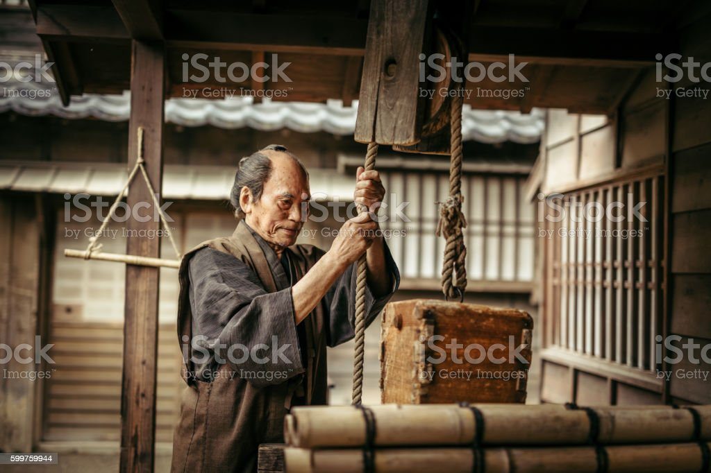 Japanese man collecting water, water well and bucket stock photo