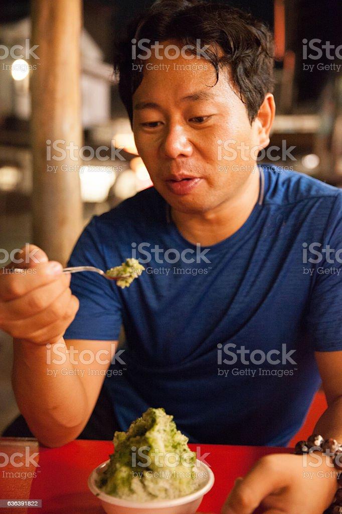 Japanese man eating shaved ice stock photo