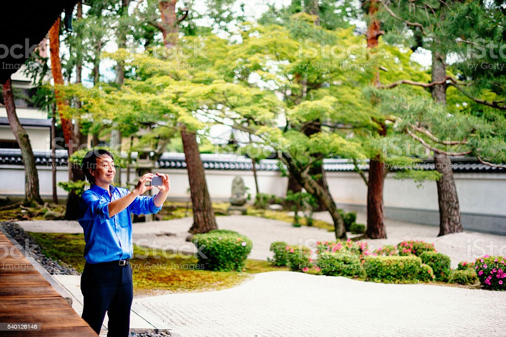 Japanese man in Chijon-ji Shrine taking photos on sunny day stock photo
