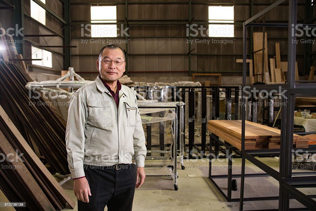 Japanese man in his 50's in an industrial setting stock photo