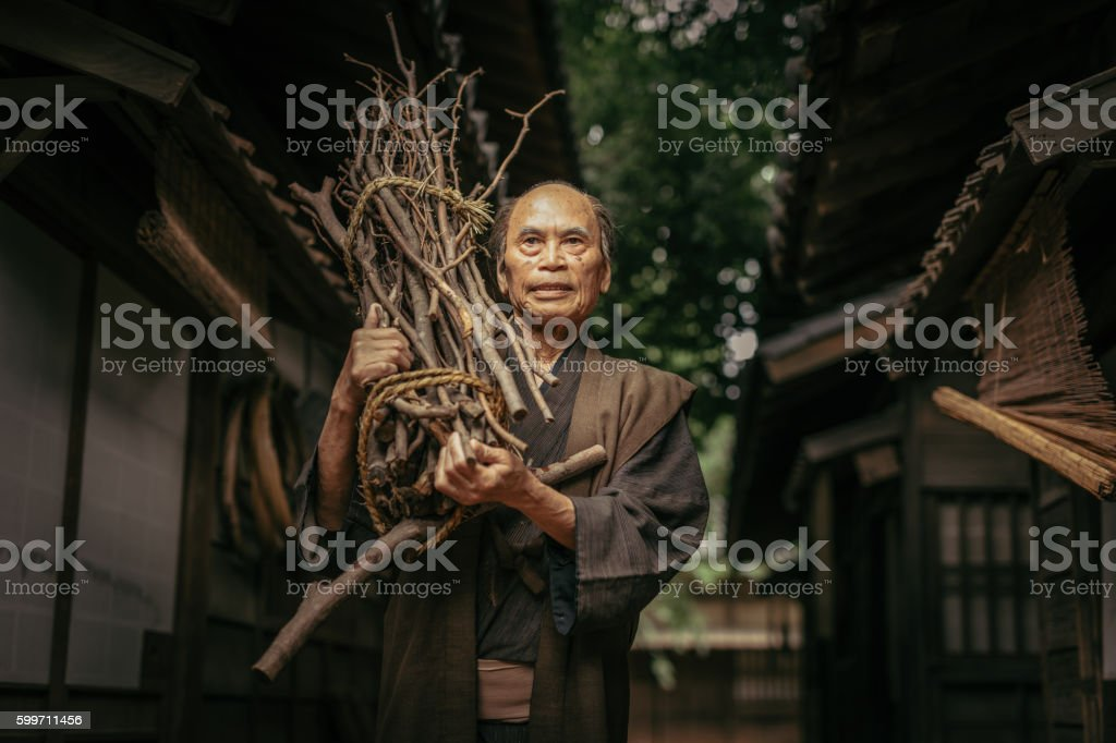 Japanese Man in traditional clothes carrying firewood stock photo