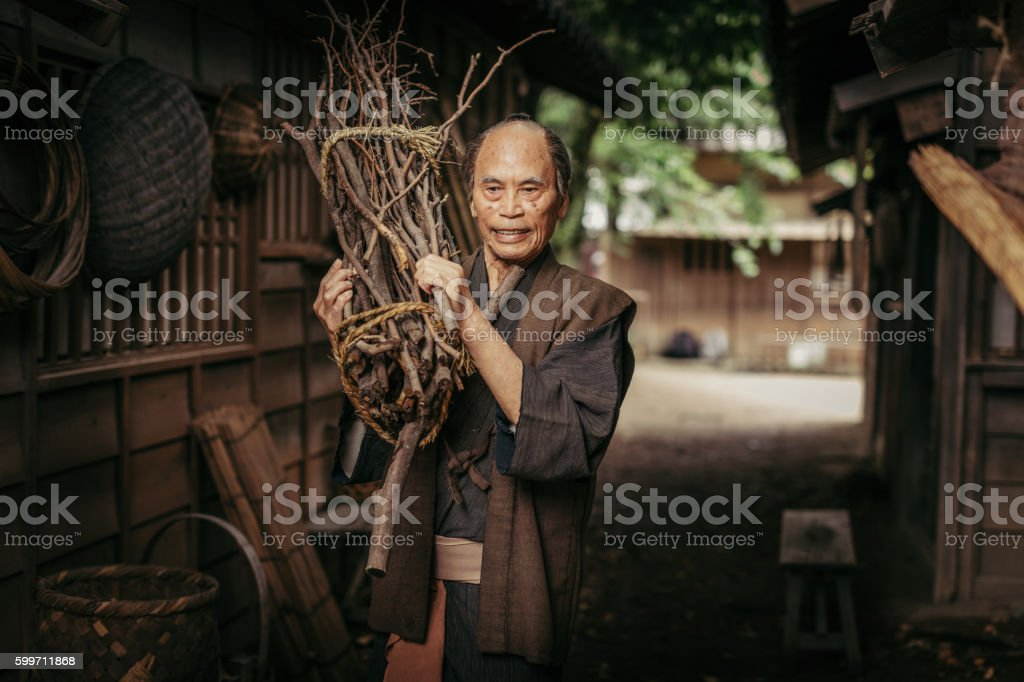 Japanese Man in village carrying firewood stock photo