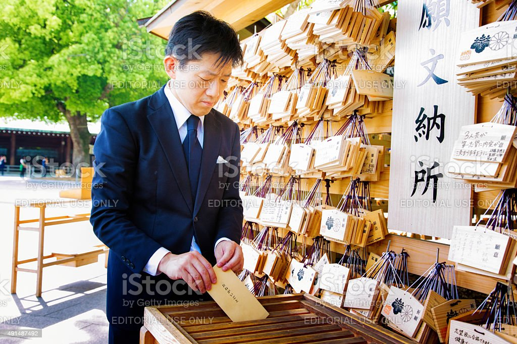 Japanese man places wish note while visiting shrine stock photo