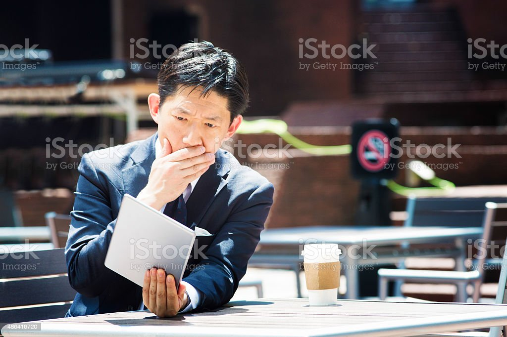 Japanese man shocked by bad news reading on tablet outdoors stock photo