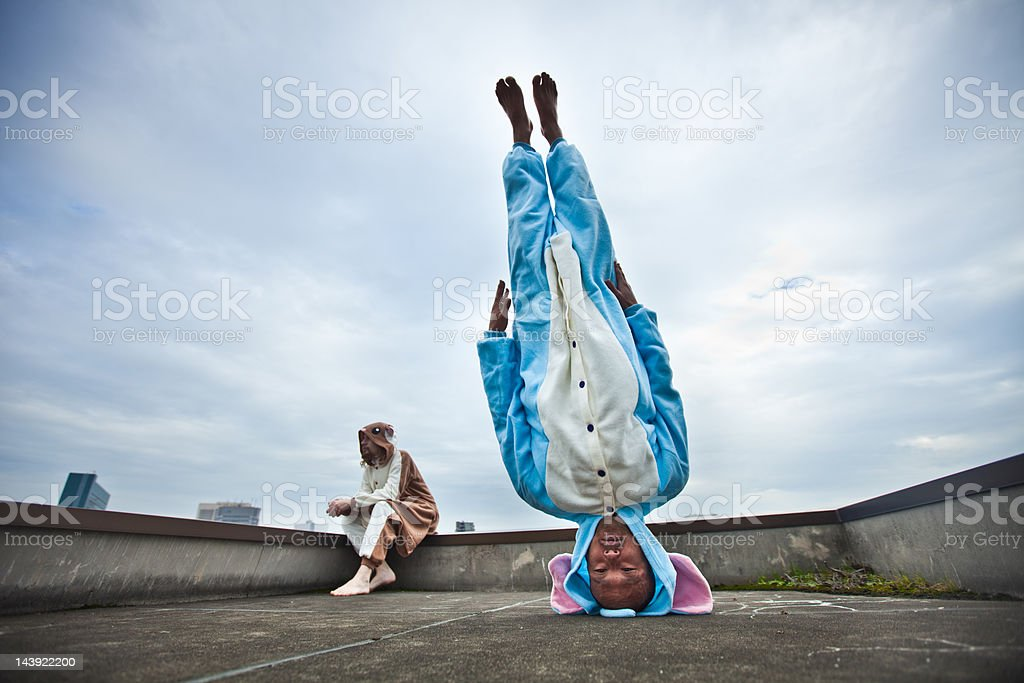 Japanese man standing on his head in elephant costume stock photo