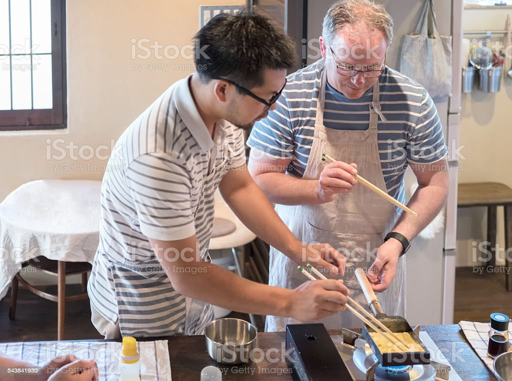 Japanese Man Teaching Caucasian Man How to Cook Tamagoyaki Omelette stock photo