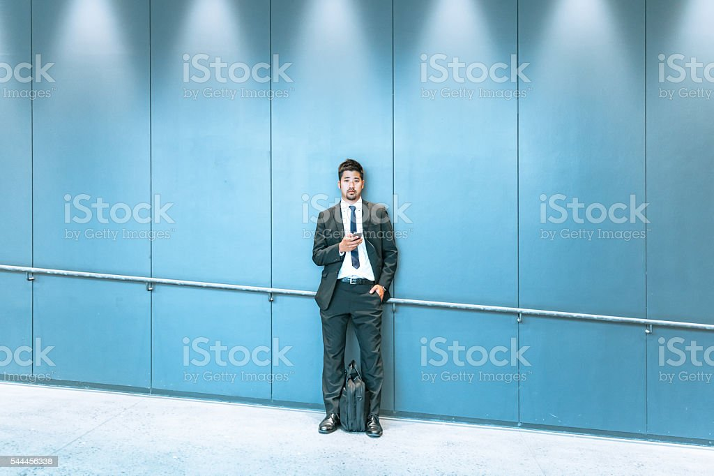 japanese man waiting against a wall stock photo