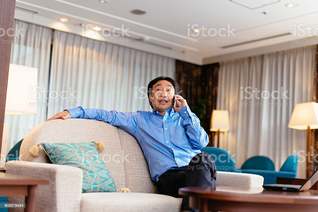 Japanese manager sitting in his cabinet and using phone stock photo