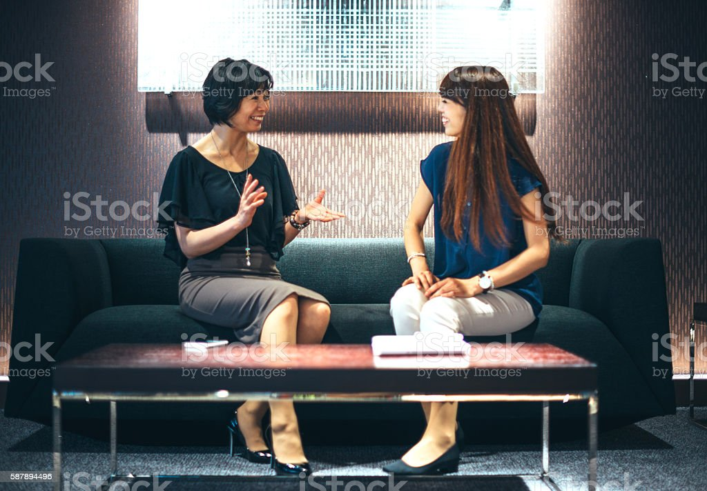 Japanese manager talks to her employee in lobby stock photo
