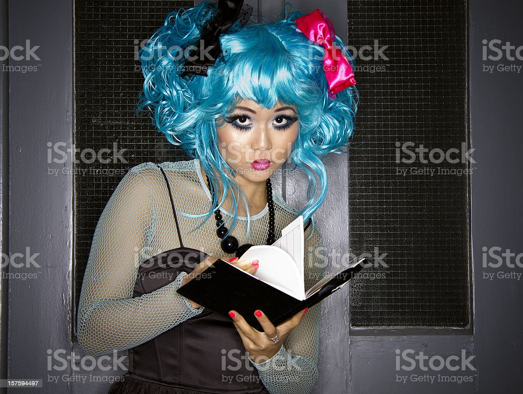 Japanese Manga Girl Flipping The Pages of Her Diary royalty-free stock photo