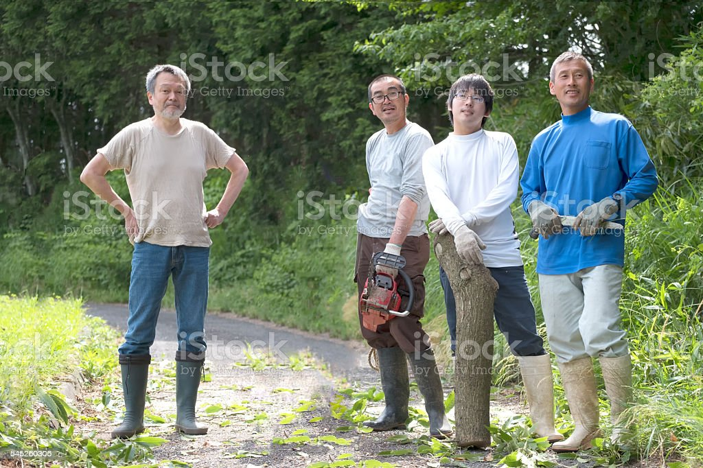 Japanese Men Neighbours Resting After Clearing Tree from Rural Road stock photo