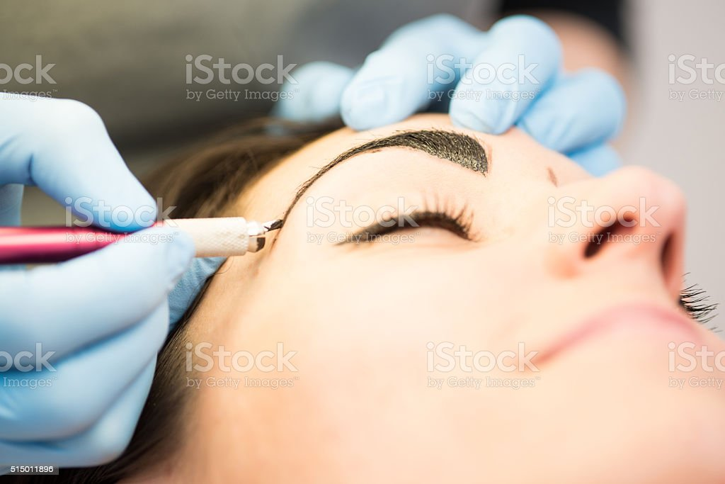 Japanese Method of Drawing Eyebrows, Close-up, Brunette in Beauty Salon stock photo
