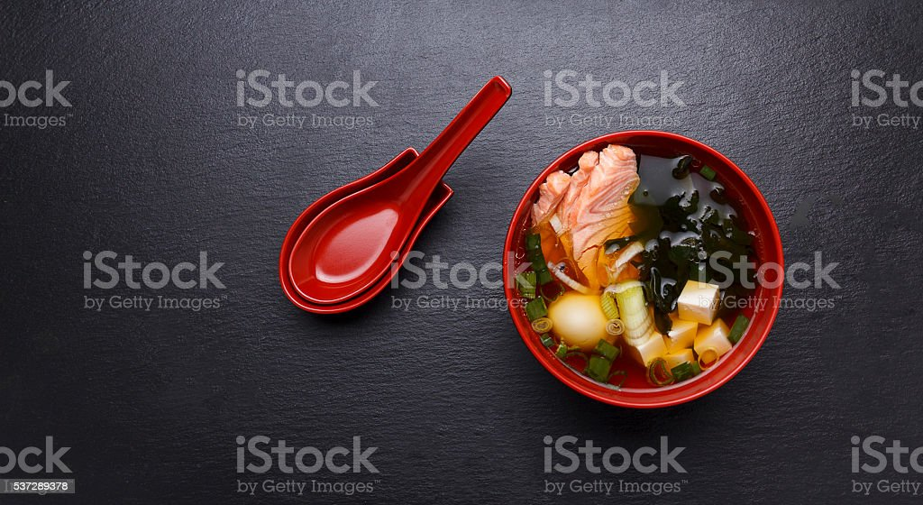 Japanese miso soup in a red bowl on the table. stock photo