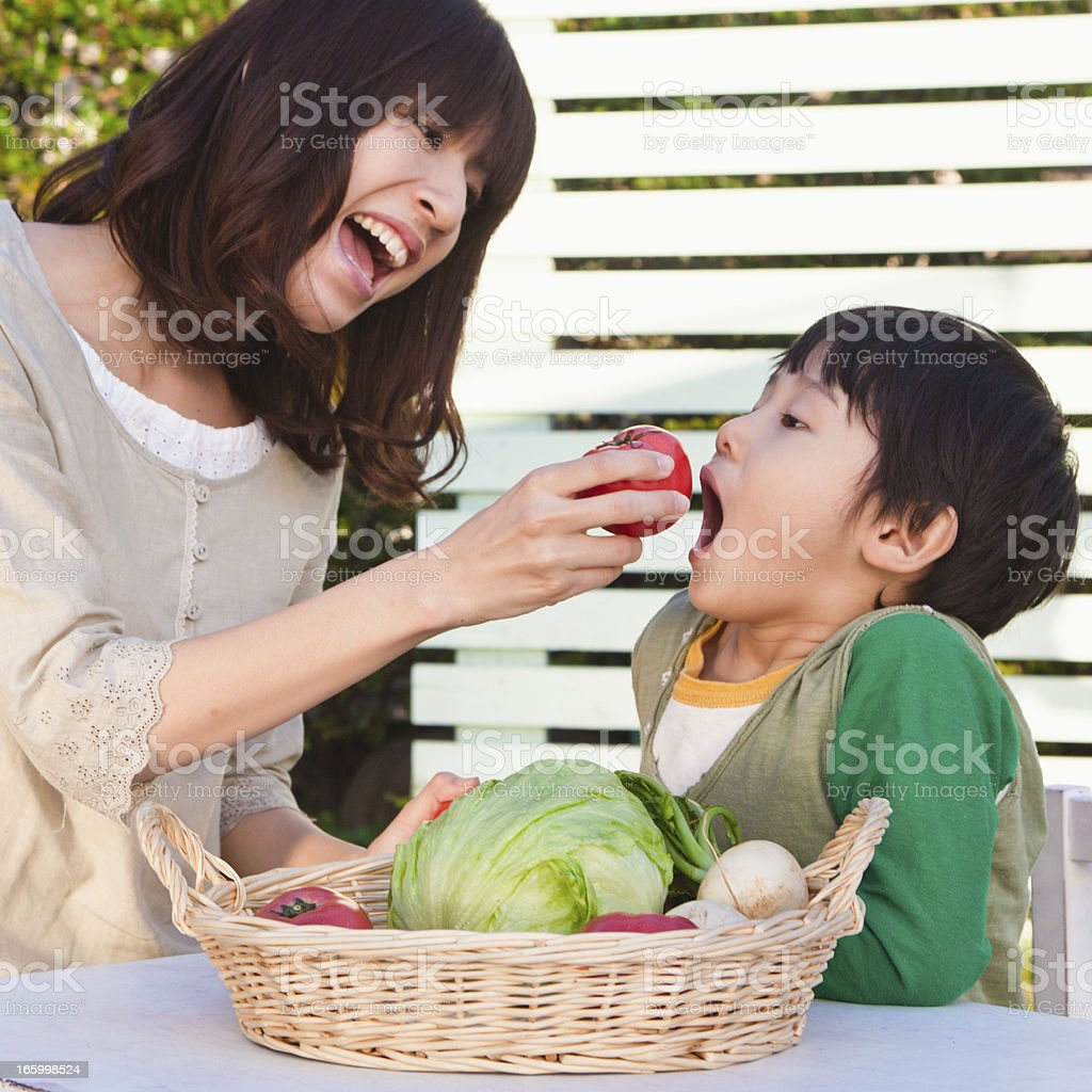 Japanese mom and son with organic vegetables in the garden. royalty-free stock photo