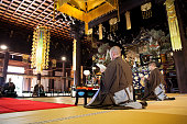 Japanese monks worshiping inside a Buddhist Temple