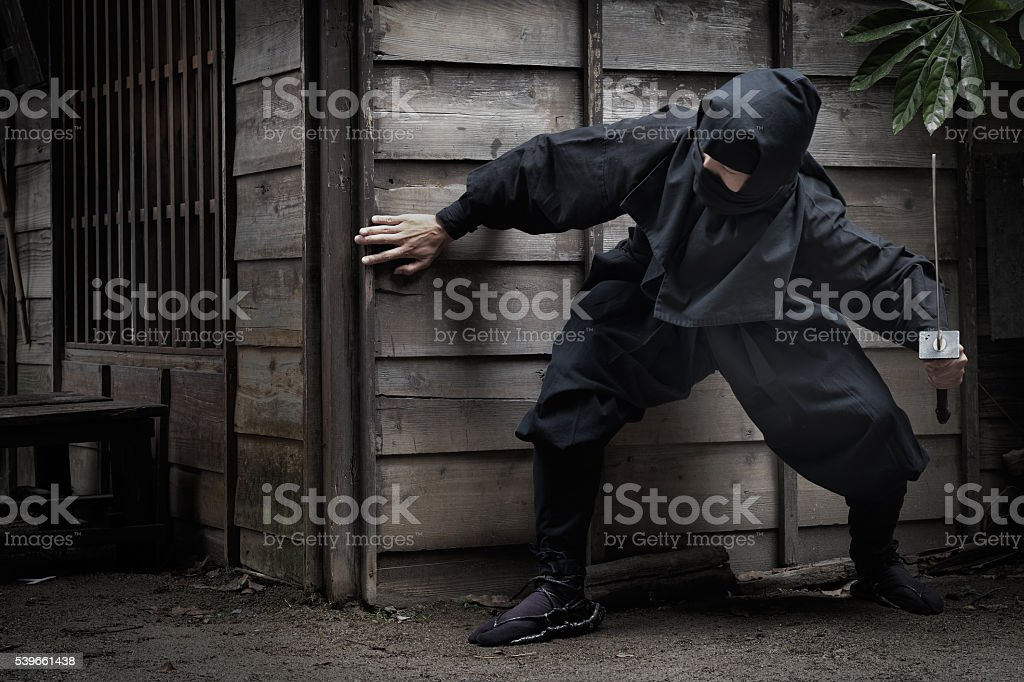 Japanese Ninja with Sword Hiding Behind Building Ready to Ambush stock photo