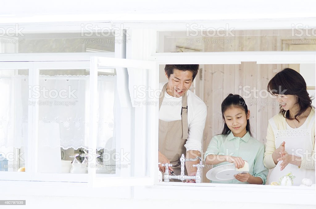 Japanese parents and daughter washing dishes in kitchen stock photo