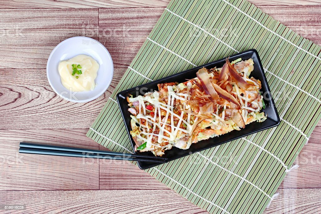 Japanese pizza (Okonomiyaki in Japanese) served with side dish. stock photo
