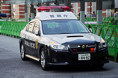 Japanese policemen people driving cop car on the road